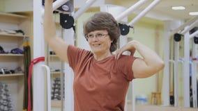 La mujer mayor que estira hacia fuera, haciendo la fisioterapia ejercita en sitio de la aptitud Gimnasia sana Mayores activos almacen de metraje de vídeo