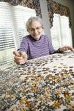 La mujer mayor que hacía la plantilla vio rompecabezas Fotografía de archivo libre de regalías