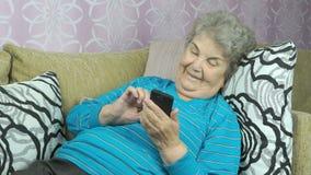 La mujer mayor que miente en un sofá del beige sostiene un teléfono móvil almacen de metraje de vídeo