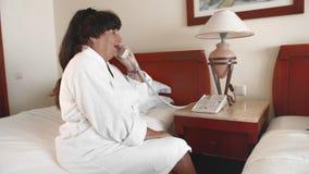 La mujer mayor que se sienta en una cama en un hotel en una albornoz blanca y toma una llamada de teléfono C?mara lenta almacen de metraje de vídeo