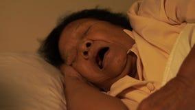 La mujer mayor que sufre de insomnio está intentando dormir en cama en cerca almacen de metraje de vídeo