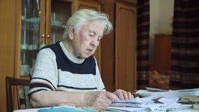 La mujer mayor que trabaja con los documentos almacen de video