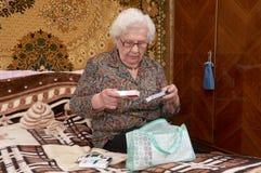 La mujer mayor saca píldoras fotos de archivo libres de regalías