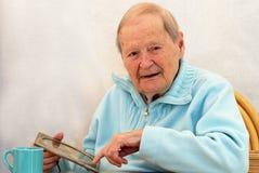 La mujer mayor señala el phothograph foto de archivo