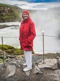 La mujer mayor se está colocando en una cascada de Gullfoss - Islandia Foto de archivo
