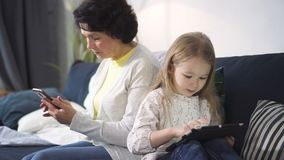 La mujer mayor se está sentando en el sofá y está mirando smartphone mientras que la chica joven está mirando algo interesante en metrajes