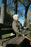 La mujer mayor se relaja en un banco Fotografía de archivo libre de regalías
