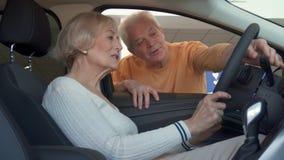 La mujer mayor se sienta dentro del coche almacen de video