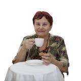 La mujer mayor se sienta en la tabla de té Imagenes de archivo