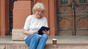 La mujer mayor se sienta en los pasos y tableta con y el café de consumición Edificio del vintage en el fondo almacen de video