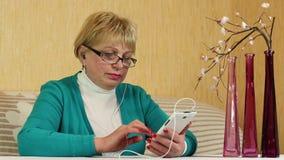 La mujer mayor se sienta en un diván y utiliza el teléfono móvil blanco metrajes