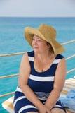 La mujer mayor sonriente en el mar vara lokking lejos Imagen de archivo libre de regalías