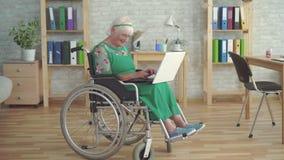 La mujer mayor sonriente feliz inhabilitó en una silla de ruedas utiliza un ordenador portátil almacen de metraje de vídeo