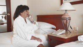 La mujer mayor sonriente feliz que se sienta en una cama en un hotel en una albornoz blanca y toma una llamada de teléfono r almacen de metraje de vídeo