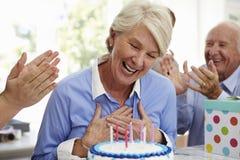 La mujer mayor sopla hacia fuera velas de la torta de cumpleaños en el partido de la familia Fotos de archivo libres de regalías