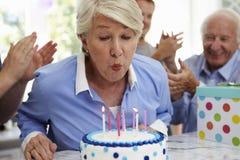 La mujer mayor sopla hacia fuera velas de la torta de cumpleaños en el partido de la familia fotos de archivo