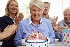 La mujer mayor sopla hacia fuera velas de la torta de cumpleaños en el partido de la familia imagenes de archivo