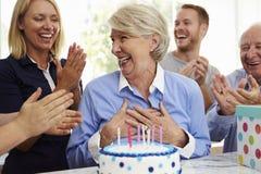 La mujer mayor sopla hacia fuera velas de la torta de cumpleaños en el partido de la familia imagen de archivo