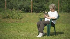La mujer mayor sostiene una tableta del ordenador al aire libre almacen de video