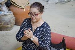 La mujer mayor tailandesa asiática ruega y espect con la estatua y dios de Buda Imagen de archivo libre de regalías