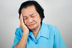 La mujer mayor tiene un dolor de cabeza imagenes de archivo