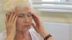 La mujer mayor tiene un dolor de cabeza metrajes