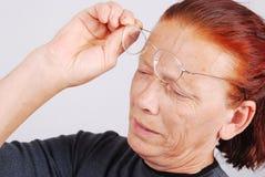 La mujer mayor tiene un problema con la vista, vidrios foto de archivo