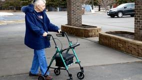 La mujer mayor utiliza a un caminante mientras que camina afuera en un estacionamiento almacen de video