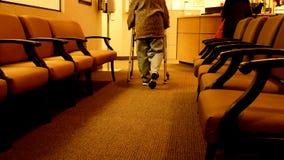 La mujer mayor utiliza a un caminante mientras que camina hacia una enfermera en la clínica imágenes de archivo libres de regalías