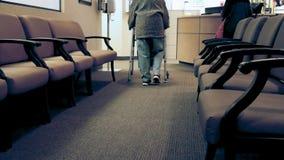 La mujer mayor utiliza a un caminante mientras que camina hacia una enfermera metrajes