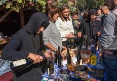 La mujer mayor vierte el vino rojo hecho en el convento, durante el festival de Georgia Foto de archivo