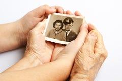 La mujer mayor y un niño están sosteniendo una foto vieja fotos de archivo libres de regalías