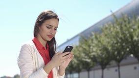 La mujer mecanografía algo en su teléfono que se sienta afuera almacen de video