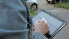 La mujer mecanografía los textos en la PC de la tableta que camina al aire libre almacen de metraje de vídeo