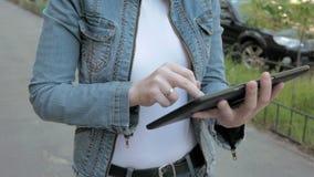 La mujer mecanografía los textos en la PC de la tableta que camina al aire libre almacen de video