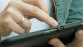 La mujer mecanografía los textos en la PC de la tableta que camina al aire libre metrajes
