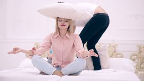 La mujer medita con una almohada en su cabeza mientras que el padre y el muchacho saltan en la cama Familia feliz en el dormitori metrajes