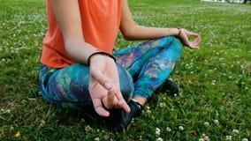 La mujer medita y hacer yoga dobla sus manos en el namaste que se sienta en el cierre de la posición de loto para arriba en la hi metrajes