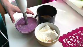 La mujer mezcla la licuadora con la gelatina, el atasco y el requesón disueltos almacen de video