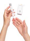 La mujer mide el nivel de la glucosa en sangre Foto de archivo libre de regalías