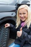 La mujer mide la pisada del neumático de un neumático de coche Fotos de archivo