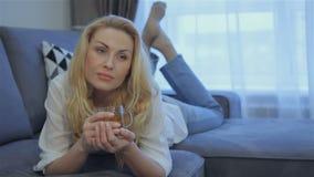 La mujer miente en su estómago en el sofá en casa almacen de video