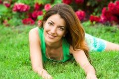 La mujer miente en una hierba imagen de archivo