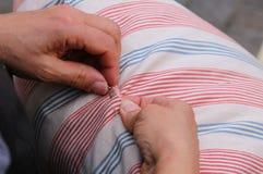la mujer mientras que cose con la aguja y rosca la almohada Imagen de archivo libre de regalías