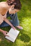 La mujer mira abajo un libro mientras que se sienta en hierba Foto de archivo libre de regalías