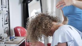La mujer mira al espejo y disfruta de su nuevo estilo después de hacer el peinado afro en el salón de belleza, muchacha sonriente almacen de metraje de vídeo