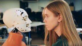 La mujer mira la cara de un robot Ser humano y robot metrajes