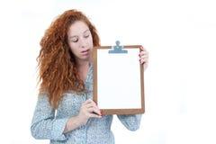 La mujer mira el espacio disponible para el anuncio Un redheade Imagenes de archivo
