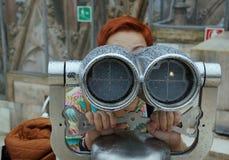 La mujer mira en el binóculo Fotografía de archivo