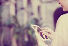 La mujer mira en el mapa de la ciudad del teléfono fotos de archivo libres de regalías